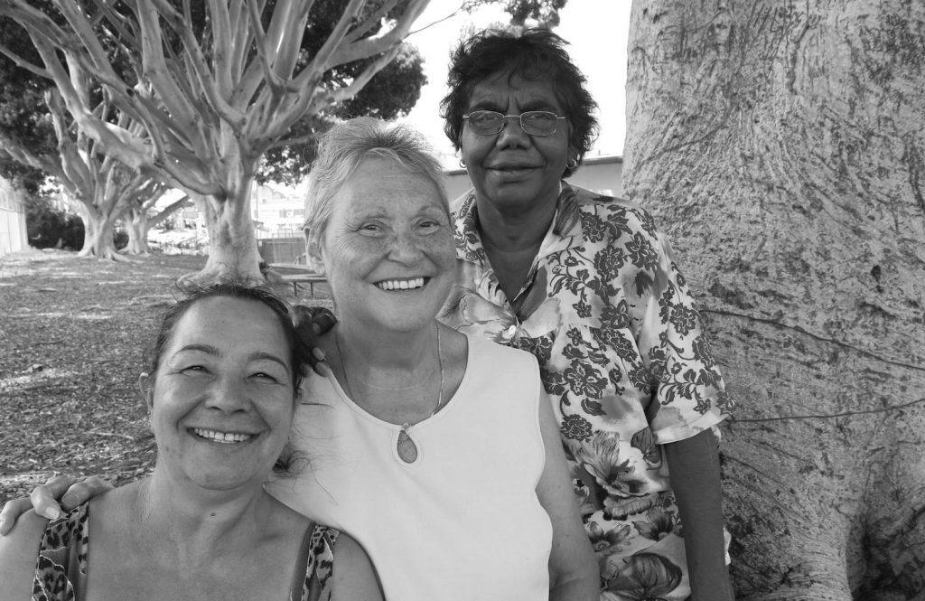 GRoup shot of three women beside a tree