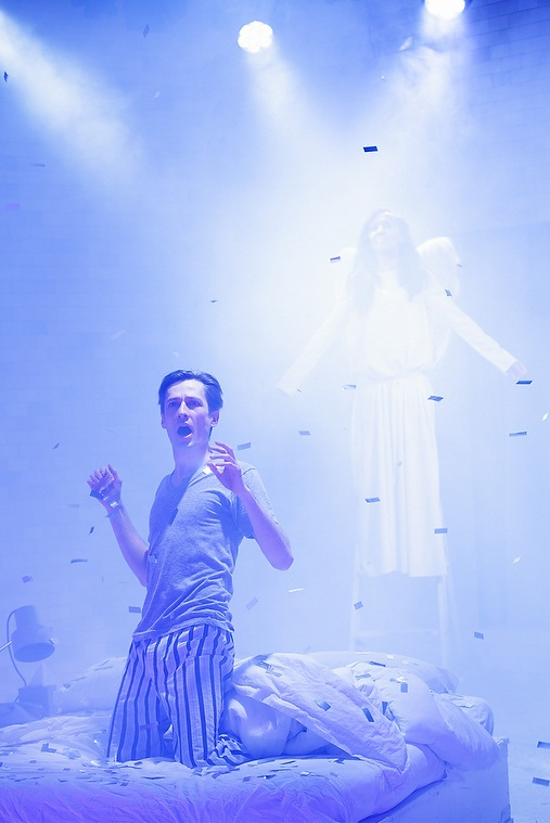 Man kneels on stage in front of luminous angel